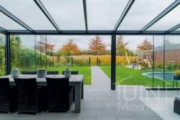 Moderne Gumax® Overkapping aan huis in mat antraciet van 8,06 x 4 meter met glazen dakplaten inclusief Gumax LED verlichting, glazen schuifwanden en Glazen spie