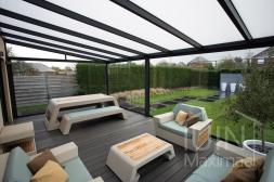 Moderne Gumax® Terrasoverkapping in mat antraciet van 7,06 x 4 meter met opaal polycarbonaat dakplaten inclusief Gumax LED verlichting, glazen schuifwanden en Glazen spie