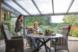 Moderne Gumax® Terrasoverkapping in mat antraciet van 6,06 x 3,5 meter met een ingekorte breedte met opaal polycarbonaat dakplaten inclusief Gumax glazen, LED verlichting schuifwanden en glazen spie