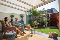 Moderne Gumax® Terrasoverkapping in mat crème van 4,06 x 3,5 meter iq-relax polycarbonaat dakplaten inclusief Gumax LED verlichting, glazen schuifwanden en polycarbonaat spie op schutting.