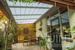 Klassieke Gumax® Terrasoverkapping in mat wit van 5,06 x 2,5 meter met glazen dakplaten en automatische zonwering