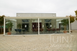 Klassieke Gumax® Overkapping aan huis in mat creme van 8,06 x 3,5 meter met glazen dakplaten inclusief Gumax glazen schuifwanden en glazen spie