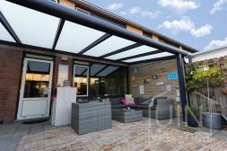 Moderne Gumax® Terrasoverkapping in mat antraciet van 6,06 x 3,5 meter met melkglas dakplaten