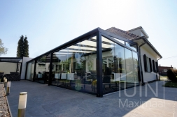 Moderne Gumax® Terrasoverkapping in mat antraciet van 12,06 x 4 meter met opaal polycarbonaat dakplaten inclusief Gumax LED verlichting, glazen schuifwanden en Glazen spie