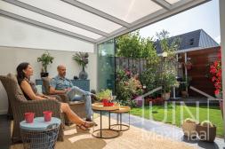 Witte aluminium overkapping aan huis met glazen schuifwanden in de tuin